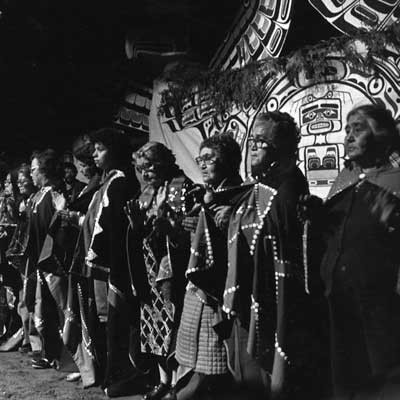 Black and White photograph of potlatch singing mourning songs at Owaxalagalis, Chief Roy Cranmer's Potlatch, 1980.