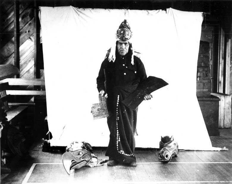 Figure stands before a white backdrop, ermine trimmed frontlet, holding two coppers with an eagle and wolf mask at his feet.