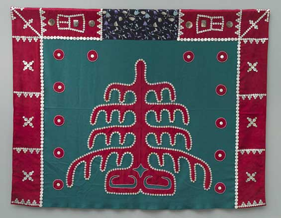 Button blanket with red frame on top and sides, green centers square with tree of life pattern and decoration.