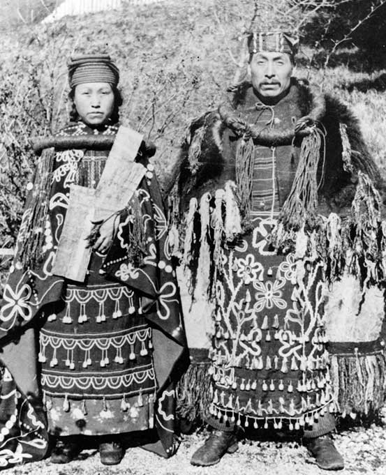 Couple stand side by side in cedar bark regalia, dance aprons, button blankets, she holds a copper in front of her chest.