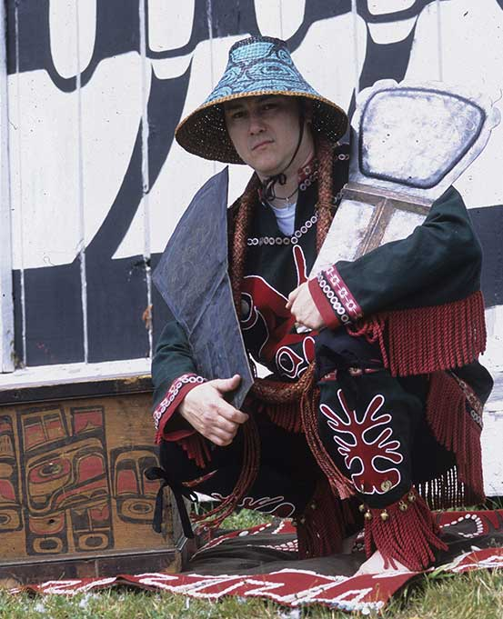 Figure holds two coppers in arms, stands before big house wearing button blanket and woven cedar hat.
