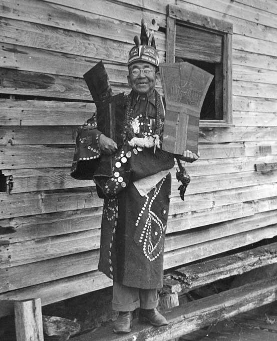 Chief Seaweed stands before a wood building, wearing a button blanket, ceremonial frontlet and holds a copper in each arm.