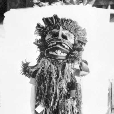 Figure is standing before a white backdrop, body covered with cedar bark fringes, wearing a mask that conceals his face.