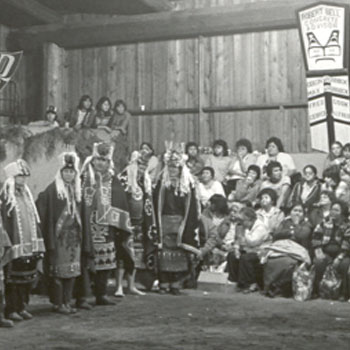 Black and white photograph shows large group of potlatchers wearing ceremonial regalia in a big house.