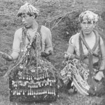 Black and white photograph of two young men in cedar bark regalia, neck rings, woven hat and dance apron.