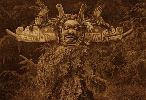 Sepia tone photograph of dancer in Sisiyutł mask with body covered in hemlock branches.