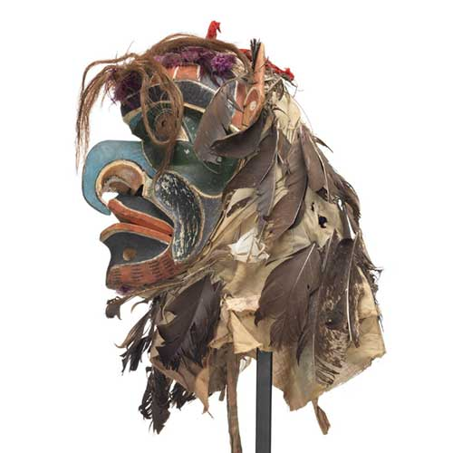 Bakwas mask, beak-like blue hooked nose, perforated brass disk for eyes surrounded by dark green patches, red, white and black facial markings, head covering of feathers mixed with hair, brightly coloured ribbons and cloth, sharp pointed ears.