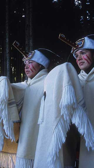 Two weather dancers in white wool and fur regalia, fur headdress and face paint, standing in a forest.