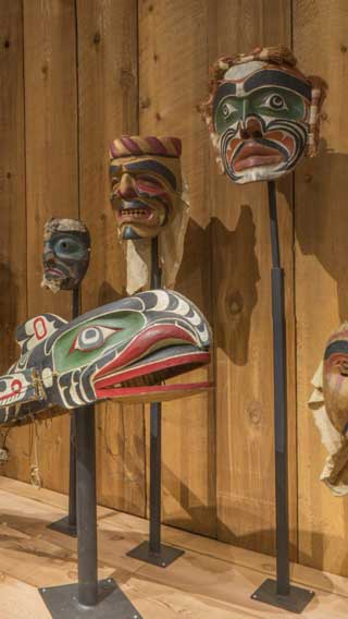 Installation photograph of the Potlatch Gallery showing a row of masks.