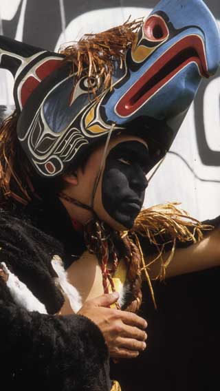 Young male dancer in black face paint wearing regalia comprised of a fur cape and thunderbird frontlet with cedar bark trim.