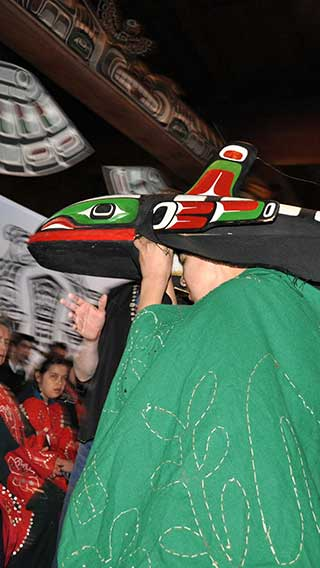 Colour photograph of dancer in whale mask, green robe, potlatch setting in big house, totem pole in background.
