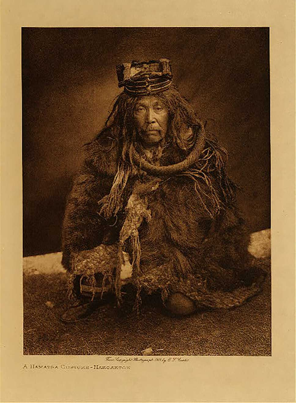 Sepia tone photograph by Edward Curtis of HAMAT´SA DANCER, 1910 in cedar regalia, crouching position, serious expression