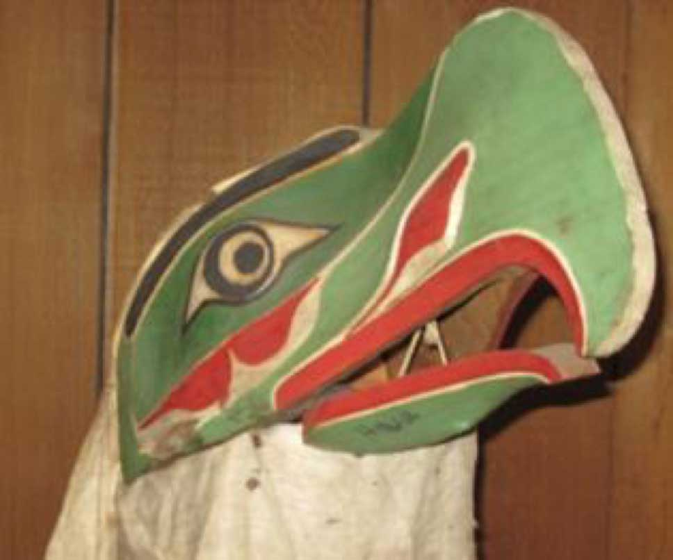 Installtion photograph of KULUS mask shot against a cedar background