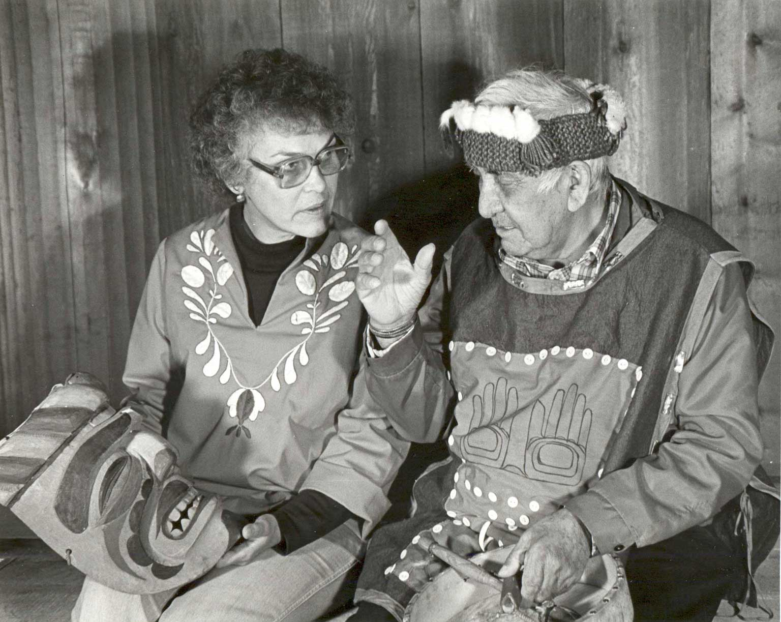 Black and white photograph shows Gloria holding Imas Mask UCC 80.01.017 while Jack - wearing a cedar bark headdress - looks on.