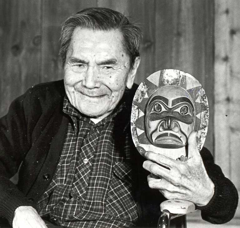 Chief Sam Scow is seated in a wheelchair, holding a frontlet close to his smiling, gentle face.