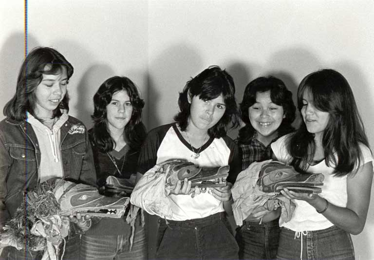Five young women - casually dressed in jeans and t-shirts - are holding 3 wolf headdresses which they look down upon with pride.