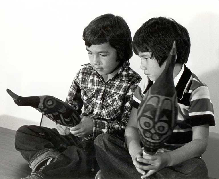 Two young boys are sitting on the floor, each holding a rattle that is shaped like a bird.
