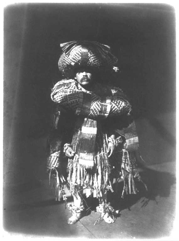 Male dancer appears standing upright, his body covered with cedar bark regalia of hat, neck ring, apron, ankle rings and blankets.