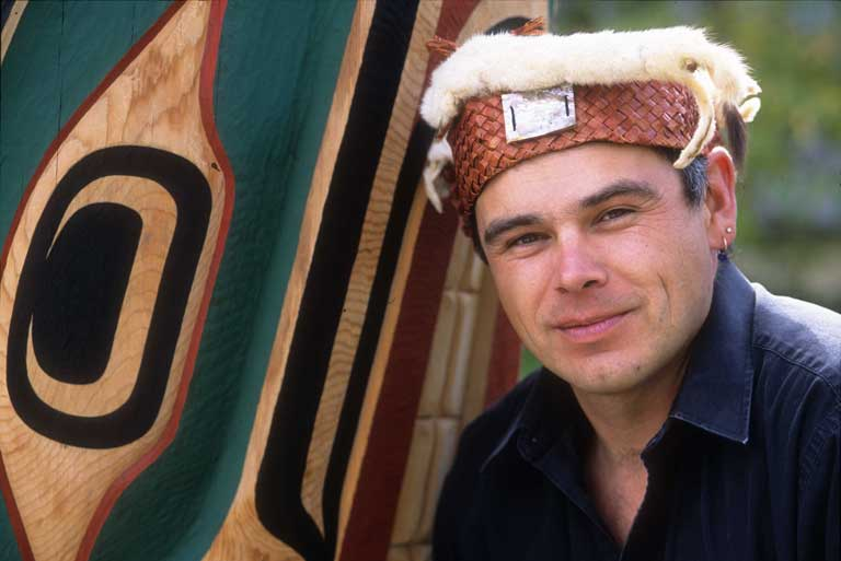 Young adult male wearing a dark blue shirt and traditional cedar frontlet with ermine trim appears before a brightly coloured wooden carving.