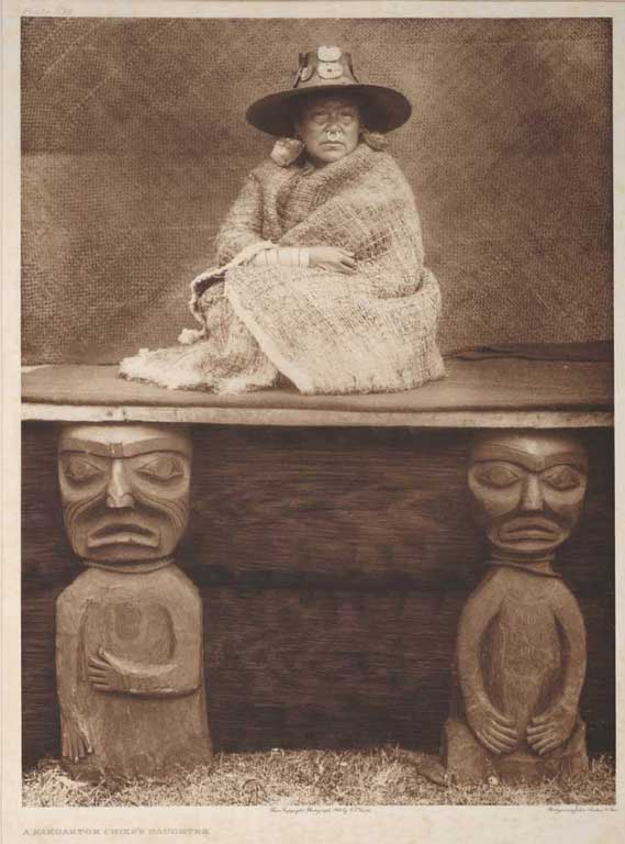 Woman seated on platform above two carved wooden figures. She wears a woven hat, large earrings, nose ring and cedar shawl.