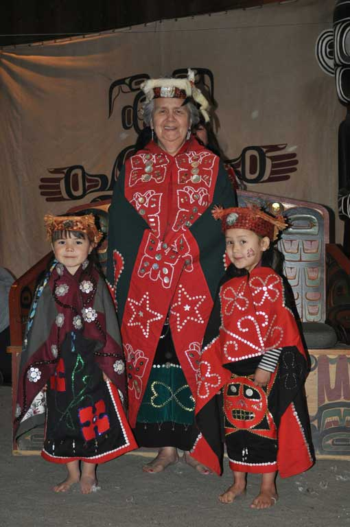 Elder Vera Newman stands in the center of the image with a young girl at each side, all are wearing regalia of button blankets and headdresses.