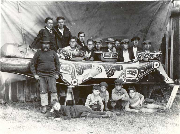 A group of boys lie seated and sprawling in front of a large carved feast dish, behind which stand 12 young men, all wearing western attire.