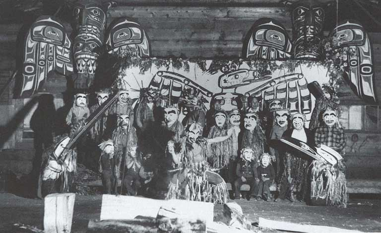 Three men in regalia dance around a fire, behind them a group of masked men stand before a painted screen and totem poles.