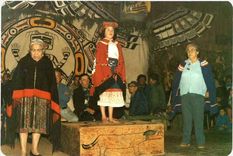 A young girl in a button blanket and cedar headdress stands on a wooden platform before a dance screen with two elders at each side.