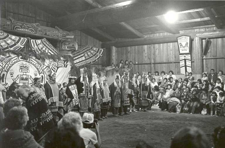 Group of dancers wearing ceremonial regalia stand before brightly painted and carved backdrop along one side of the big house.