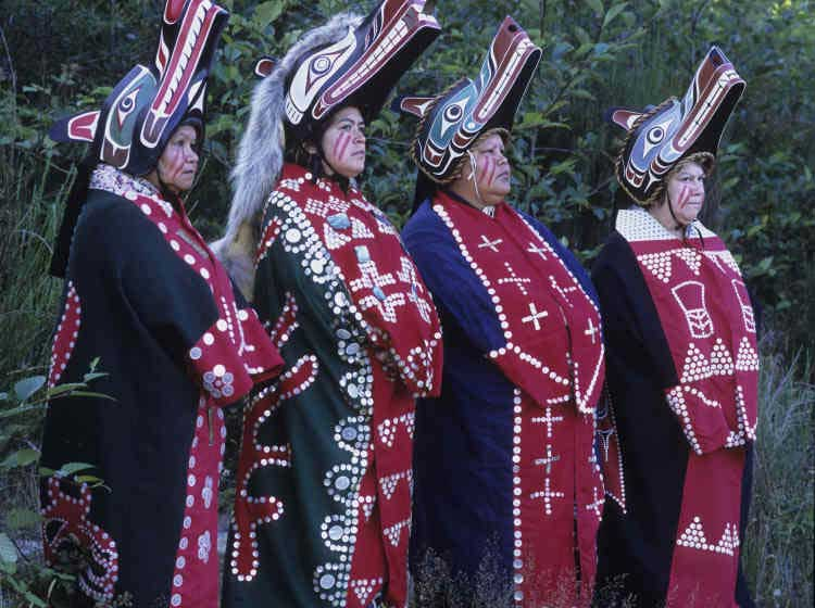 Four women stand in a row facing to the right of the camera, each wears a button blanket and a wolf headdress.