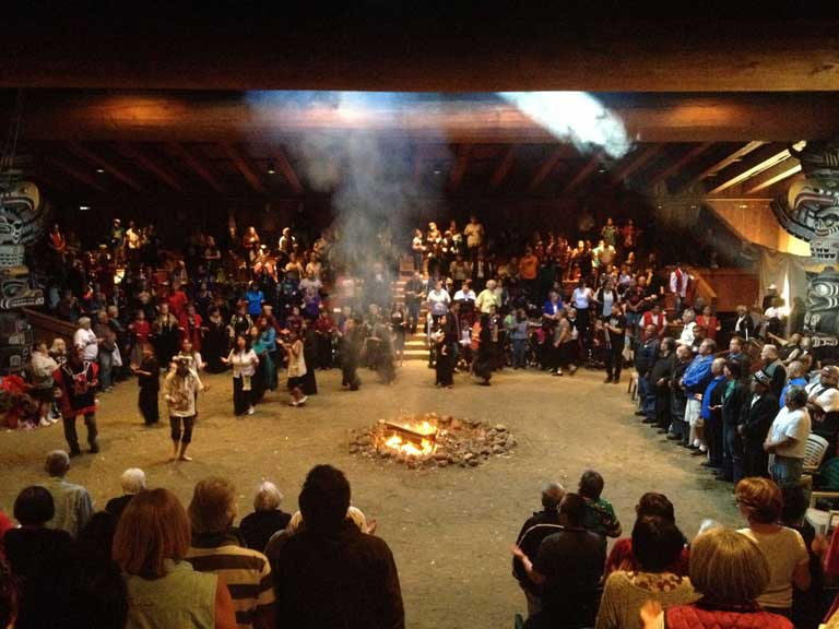 A large group of celebrants appear standing and dancing around a fire in the center of the bighouse.