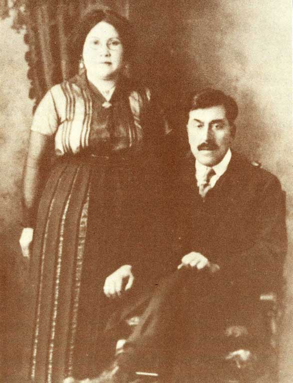 Couple are posed for a studio portrait dressed in western attire, he is seated and she stands at his side.