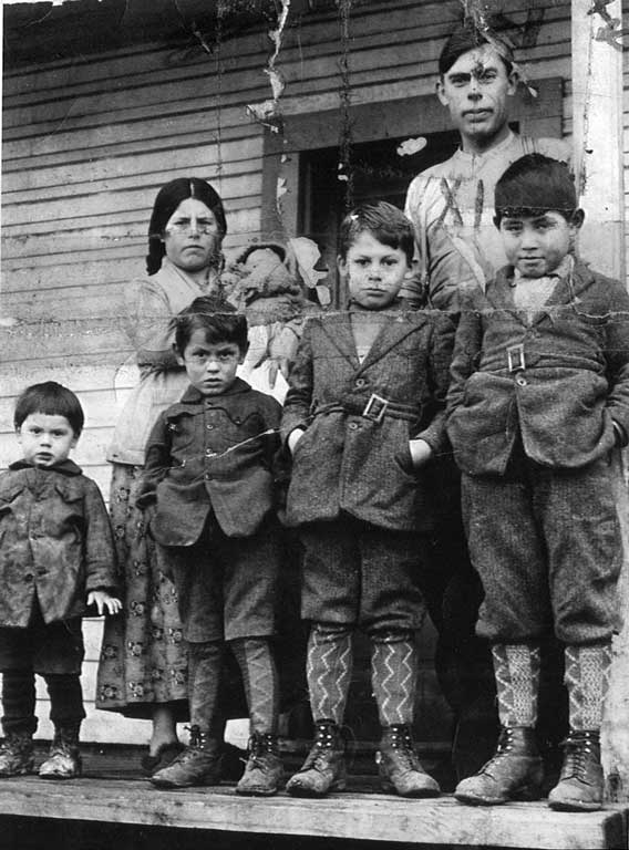 Four young boys in wool coats, knickers, socks leather boots stand before parents, the mother cradles a newborn in her arms.
