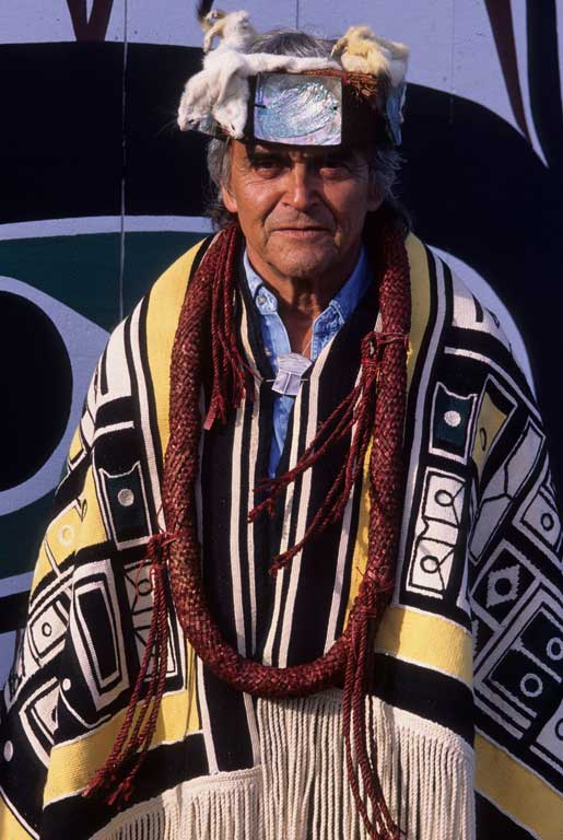 Chief Cranmer appears wearing a Chilkat blanket, cedar neck rings, a frontlet with ermine trim and mother of pearl decoration.