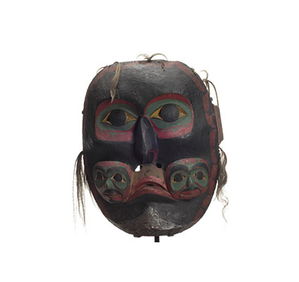 Imas - Three faced mask, large dark ancestral spirit mask two small faces carved at either side of mouth, black with green red and white details, some hair fragments.