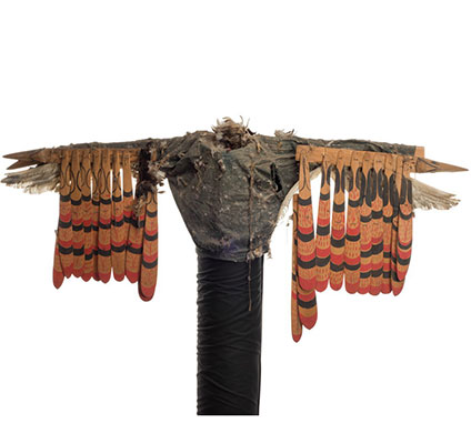 Kwigwis or sea eagle costume of denim jacket, sewn or tied bunches of feathers, painted and carved wooden feathers hung from arms.