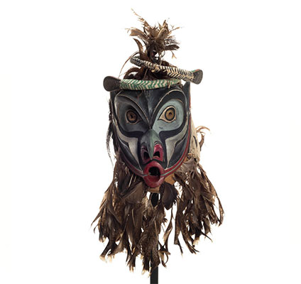 Bakwas mask with two coiled snakes atop highly arched eyebrows, brass disks with perforated centres for eyes, a beak-like nose, feather trim.