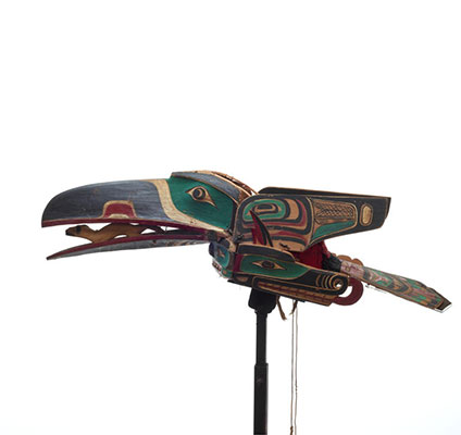 A raven mask, brightly painted with hinged wings, clasping a carved ermine figure in its beak, below which is a sisyutl or serpent figure.