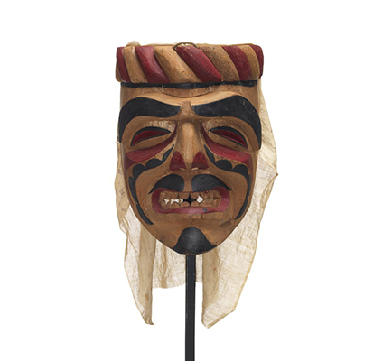 An Imas ancestor mask with a carved band atop, dramatic face paint in black and red, grimacing expression, cloth back at back.