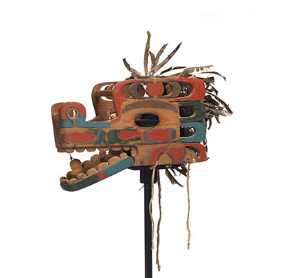 A Haietlik or serpent mask, elaborately carved with numerous cut-out parts, colourful markings in pale blue, green and red, feather trim, hinged lower jaw.