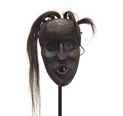 A Dzunuk´wa or wild woman of the woods mask, deep carved, dark smoky paint with dark red on nose and pursed lips, tufts of hair falling to one side.