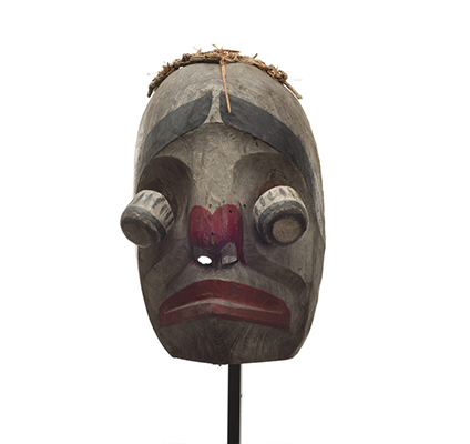 Atłak´ima or imitator mask, mostly white washed with bulging hinged eyes, red paint lips and around nostrils, thick black eyebrows and cedar bark trim.
