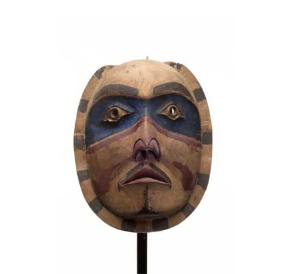 A 'Makwala or moon mask carved of cedar with blue patches around eyes and radial pattern around face.