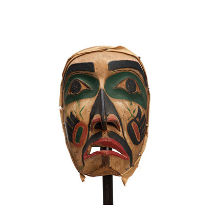 Hayakantalał, carved wood with holes for eyes and mouth, green patches around eyes, black markings with painted hand symbols on each cheek.