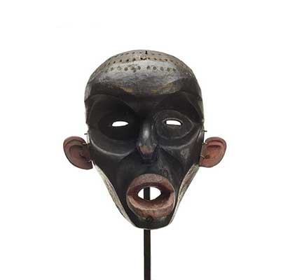 A Dzunuk´wa or wild woman of the woods mask, deep carved, dark paint with red lips cheek and ears, holes drilled in scalp where hair had been attached.