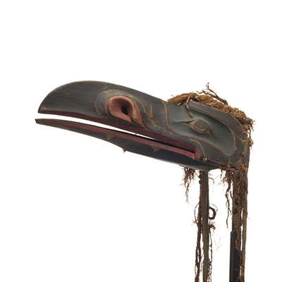 A raven headdress, dark appearance, hinged beak with green paint around eyes, red trim around beak and nostrils with thin and worn cedar trim.