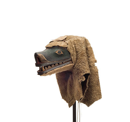 A Nanis or sea dog mask with long muzzle open mouth and sharp teeth, green paint surrounding eyes, sheep skin attached at back.