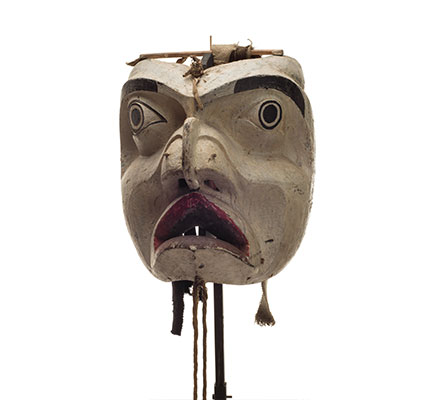 Forest spirit mask, mostly white face, deeply carved features, black paint eyebrows and around eyes, cloth and leather strips attached to back.
