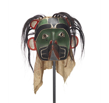 Sapagamł or echo mask, green and black with white red trim, interchangeable mouthpiece shown with raven.