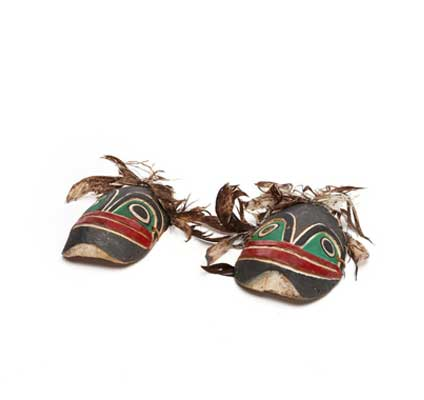 Kneecaps with frog faces, feathers attached, part of Bak´was costume, black and green with red mouth.
